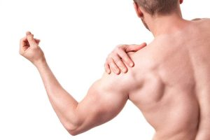 Young muscular man having pain of shoulder