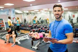 47306226 - handsome trainer using tablet in weights room at the gym