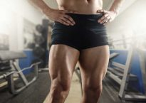 Close up of strong muscular men`s legs in the gym.